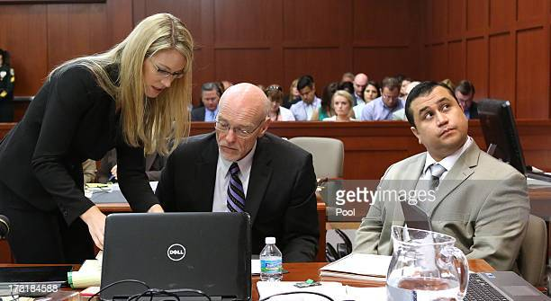 George Zimmerman looks up at a projection screen as defense counsel Don West talks to an assistant during the trial in Seminole circuit court July 9...
