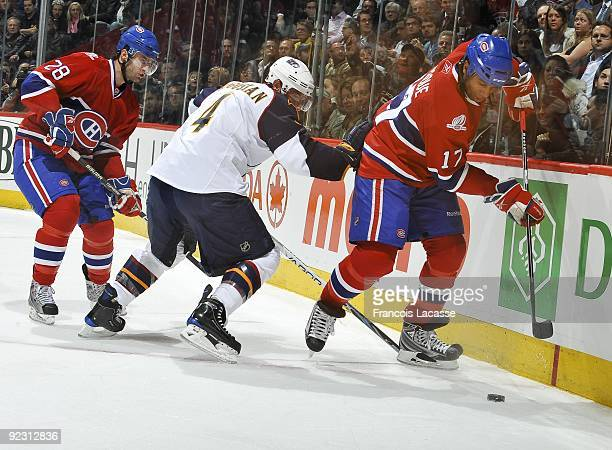 Georges Laraque of the Montreal Canadiens battles for the puck along the boardside with teammate Kyle Chipchura during the NHL game against the...