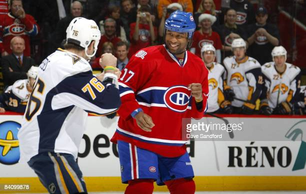 Georges Laraque of the Montreal Canadiens smiles as he fights Andrew Peters of the Buffalo Sabres during their NHL game at the Bell Centre December...