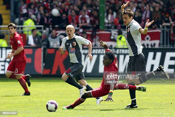 Georges Mandjeck of Kaiserslautern is challenged by Tobias Werner and Goran Sukalo of Augsburg during the Second Bundesliga match between 1. FC...