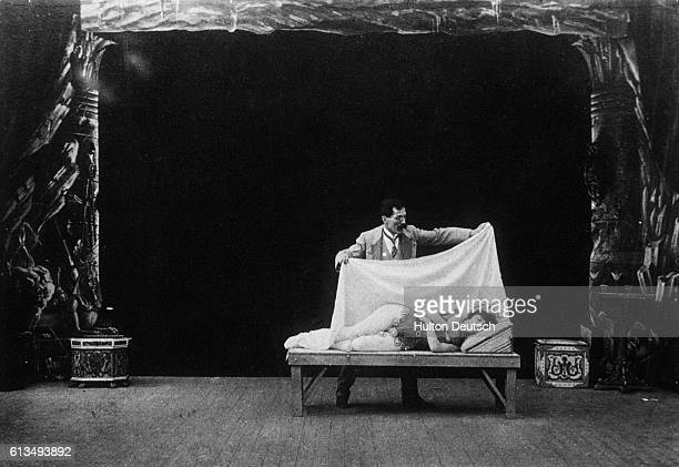 Georges Melies the early French cinematographer performing a magician's act with a female assistant