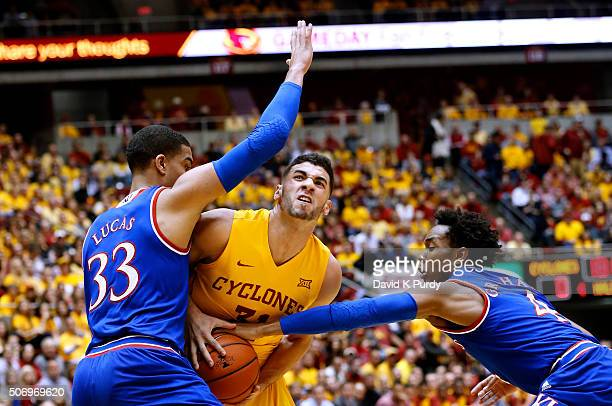 Georges Niang of the Iowa State Cyclones drives the ball as Landen Lucas of the Kansas Jayhawks blocks and Devonte' Graham of the Kansas Jayhawks...