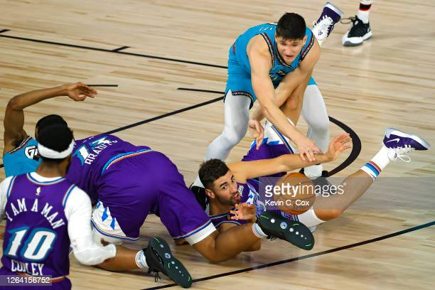 Georges Niang of the Utah Jazz grabs a loose ball in front of Grayson Allen and De'Anthony Melton of the Memphis Grizzlies during the second half at...