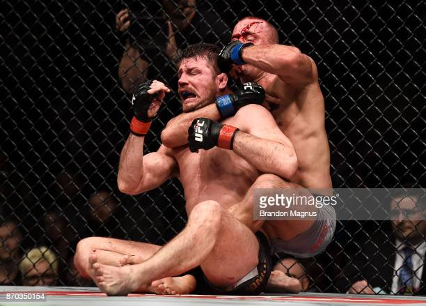 Georges StPierre of Canada attempts to submit Michael Bisping of England in their UFC middleweight championship bout during the UFC 217 event inside...