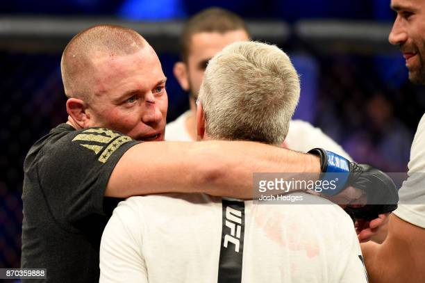 Georges StPierre of Canada celebrates with trainer Freddie Roach following hs victory over Michael Bisping of England in their UFC middleweight...