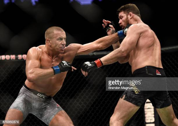 Georges StPierre of Canada punches Michael Bisping of England in their UFC middleweight championship bout during the UFC 217 event inside Madison...