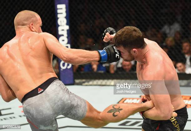 Georges StPierre of Canada punches Michael Bisping of England in their UFC middleweight championship bout during the UFC 217 event at Madison Square...