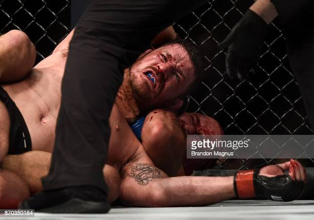 Georges StPierre of Canada submits Michael Bisping of England in their UFC middleweight championship bout during the UFC 217 event inside Madison...
