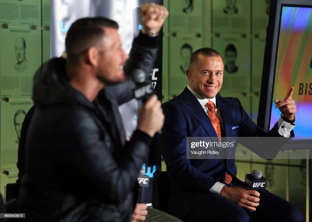 Georges St-Pierre reacts as Michael Bisping speaks to the media during the UFC 217 press conference at the Hockey Hall of Fame on October 13, 2017 in Toronto, Canada.
