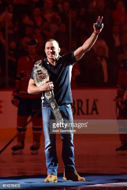 Georges StPierre salutes the crowd with his championship belt before the Columbus Blue Jackets versus the Montreal Canadiens game on November 14 at...