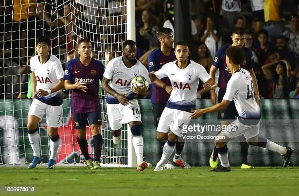 GeorgesKevin Nkoudou of Tottenham Hotspur runs with the ball upfield after scoring Tottenham's second goal as Sergi Palencia of Barcelona looks on...