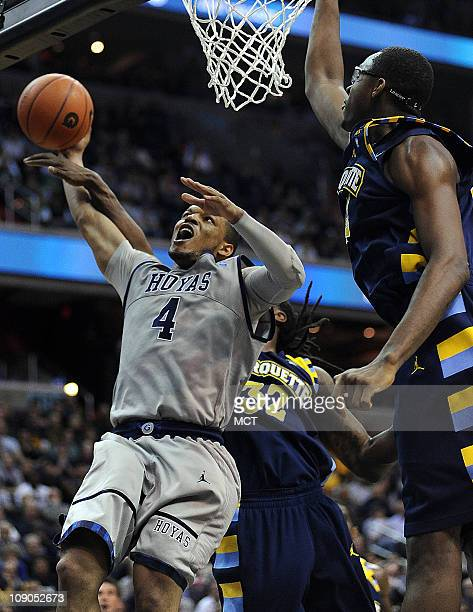Georgetown guard Chris Wright gets fouled on a drive by Marquette forward Jae Crowder as Marquette center Chris Otule right assists on defense during...