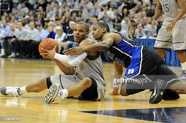 Georgetown guard Chris Wright left looks to pass the ball to a teammate while seated on he floor and defended by Duke forward Lance Thomas during...