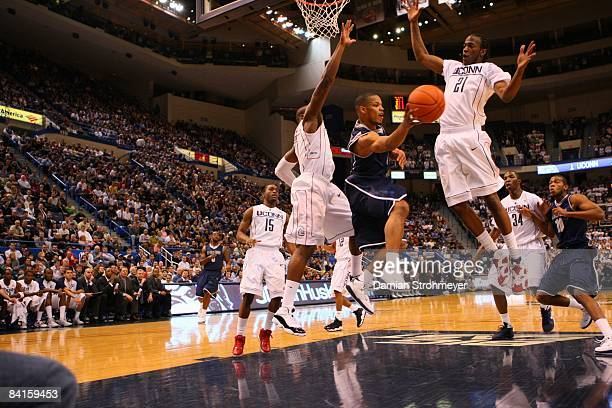 Georgetown guard Chris Wright slices between Connecticut defenders Jeff Adrien and Stanley Robinson NCAA Basketball Georgetown at UConn Monday game...