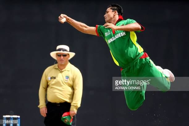 Bangkladeshi cricketer Mashrafe Mortaza is watched by umpire Mark Benson as he jumps to catch the ball against South Africa during the supereight...