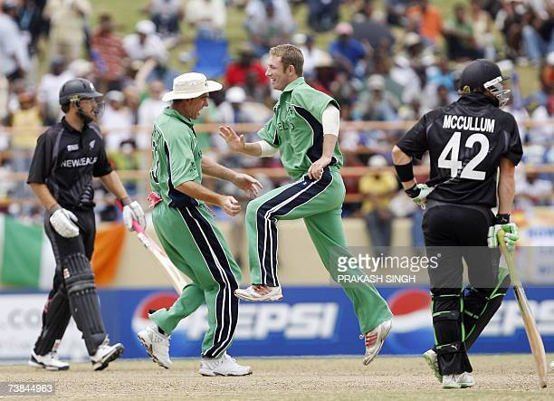 Ireland's Andrew White jumps alongside Captain Trent Johnston after taking the wicket of New Zealand's Daniel Vettori during the SuperEight match at...
