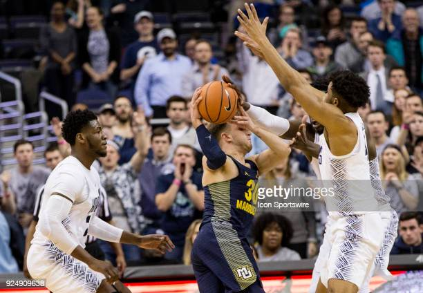 Georgetown Hoyas center Jessie Govan and Georgetown Hoyas guard Jagan Mosely reach out to block the progress of Marquette Golden Eagles guard Andrew...