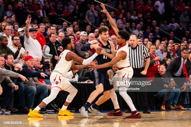 Georgetown Hoyas Guard Greg Malinowski looks to pass the ball with St John's Red Storm Guard Shamorie Ponds and St John's Red Storm Guard Justin...