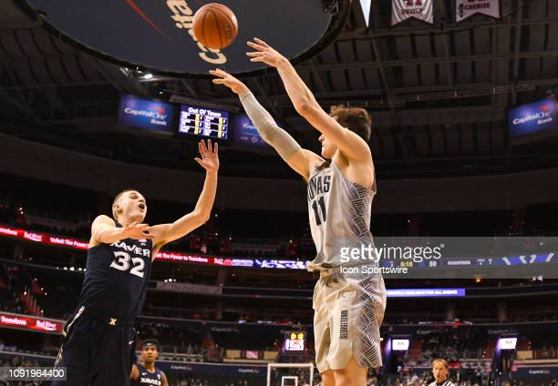 Georgetown Hoyas guard Greg Malinowski makes a three point basket in the second half against Xavier Musketeers forward Ryan Welage on January 31 at...