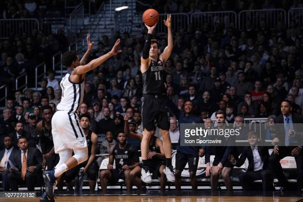 Georgetown Hoyas guard Greg Malinowski shoots a three pointer over Butler Bulldogs forward Jordan Tucker during the men's college basketball game...
