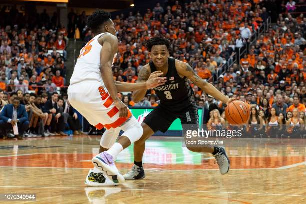 Georgetown Hoyas Guard James Akinjo dribbles the ball against Syracuse Orange Guard Tyus Battle during the first half of the Georgetown Hoyas versus...
