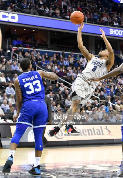 Georgetown Hoyas guard James Akinjo scores in overtime against Seton Hall Pirates guard Shavar Reynolds on March 2 at the Capital One Arena in...