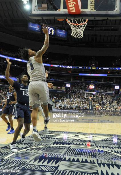 Georgetown Hoyas guard James Akinjo scores in the second half against Xavier Musketeers forward Naji Marshall on January 31 at the Capital One Arena...