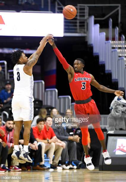 Georgetown Hoyas guard James Akinjo scores over Liberty Flames guard Lovell Cabbil Jr tin the first half on December 3 at the Capital One Arena in...