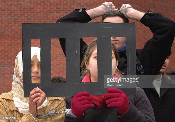 Georgetown University students Rehenuma Asmi , Suad al-Kawas and Emil Totonchi use mock jailbars and handcuffs as they participate in a demonstration...