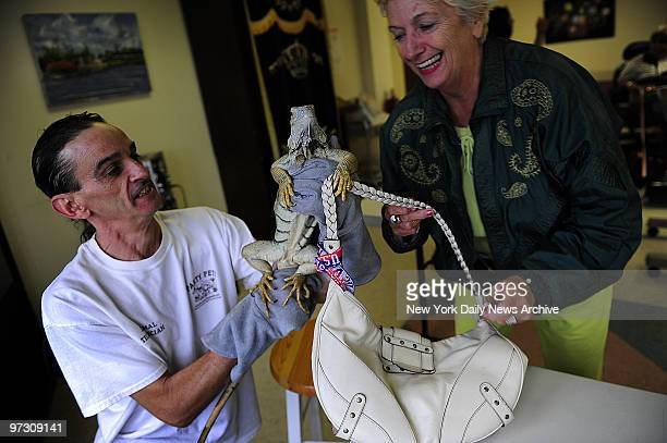 Georgette Ricaud interacts with iguana named Iggy who has grabbed her purse at Pet Therapy session at Senior home which brings peace and smiles to...