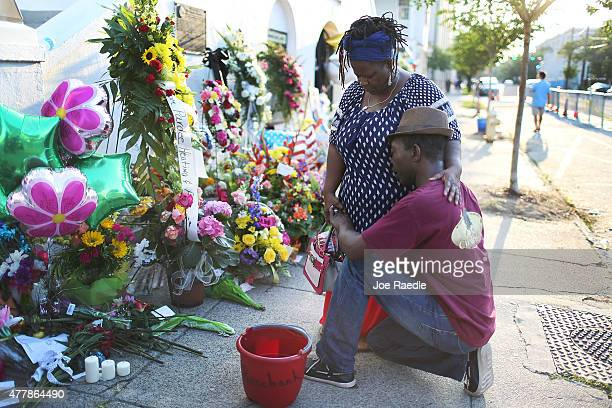Georgette Sanders and her husband Allen Sanders hug after laying flowers on the memorial in front of the Emanuel African Methodist Episcopal Church...