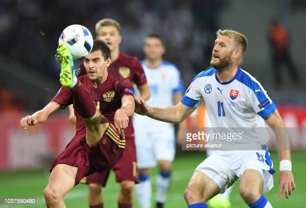 Georgi Schennikov of Russia and Adam Nemec of Slovakia vie for the ball during the UEFA Euro 2016 Group B soccer match Russia and Slovakia at Stade...