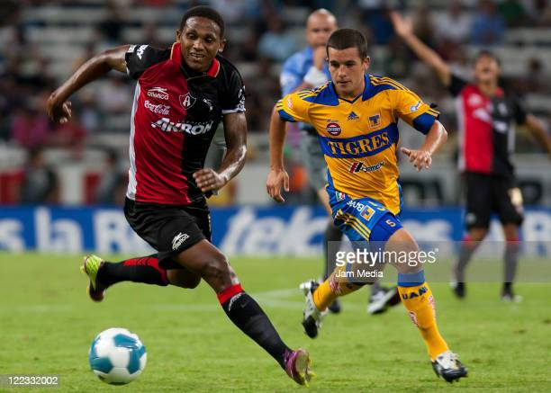 Georgi Welcome of Atlas struggles for the ball with Eder Borelli of Tigres during their match as part of the Apertura 2011 at the Jalisco Stadium on...