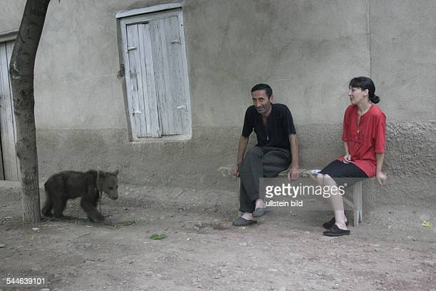 couple sitting beside a chained dancing bear in former german colony Katharinenfeld