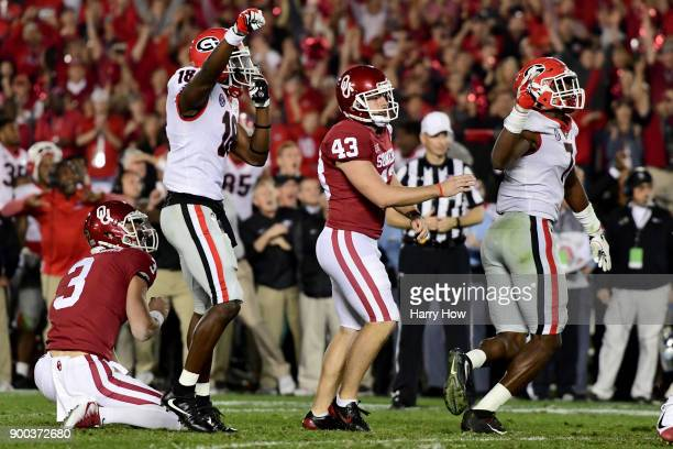 Georgia Bulldogs and Oklahoma Sooners react after Lorenzo Carter of the Georgia Bulldogs blocks the field goal attempt from Austin Seibert of the...