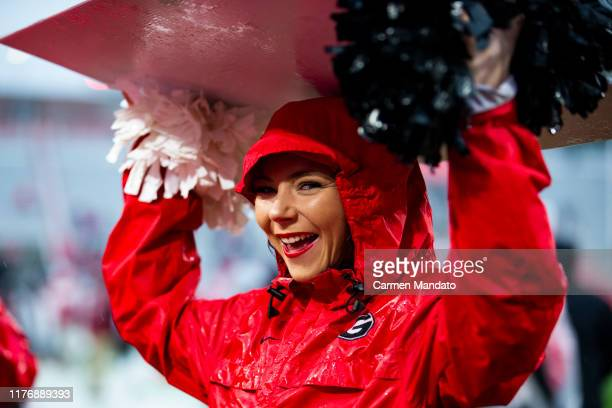Georgia Bulldogs cheerleader shields herself from the rain prior to a game against the Kentucky Wildcats at Sanford Stadium on October 19 2019 in...
