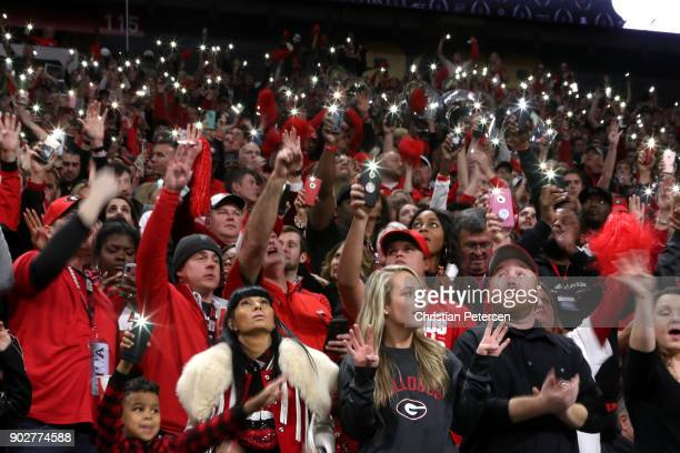 Georgia Bulldogs fans hold up their phone flashlights at the start of the fourth quarter against the Alabama Crimson Tide in the CFP National...