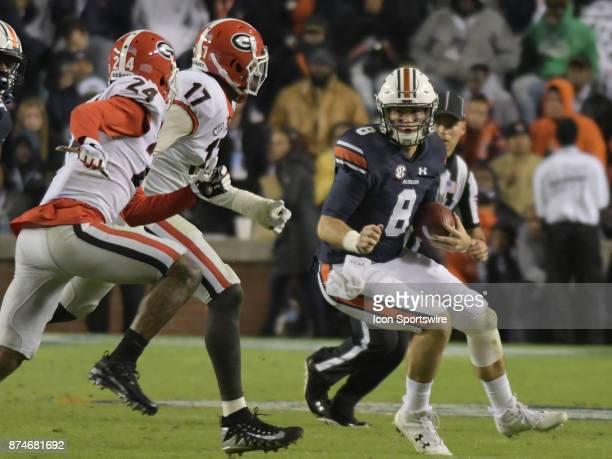 Georgia Bulldogs linebacker Davin Bellamy and Georgia Bulldogs defensive back Dominick Sanders pursues Auburn Tigers quarterback Jarrett Stidham as...