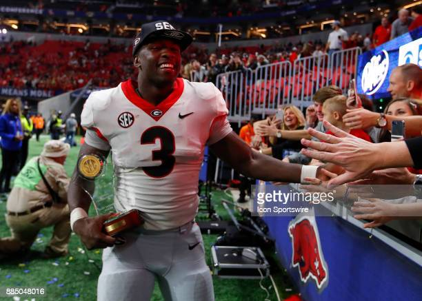 Georgia Bulldogs linebacker Roquan Smith reacts with fans while holding his Most Valuable Player trophy at the conclusion of the SEC Championship...