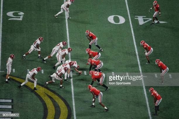 Georgia Bulldogs players and Alabama Crimson Tide players line up at the line of scrimmage during the College Football Playoff National Championship...