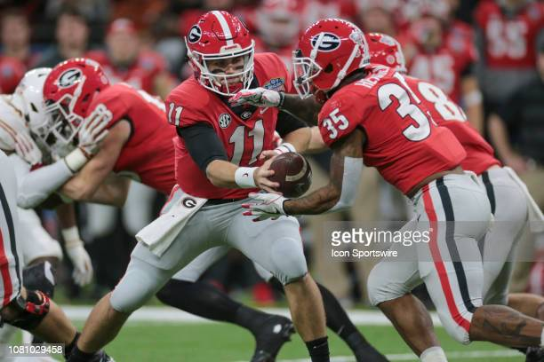 Georgia Bulldogs quarterback Jake Fromm hands off to running back Brian Herrien during the Allstate Sugar Bowl game between the Georgia Bulldogs and...