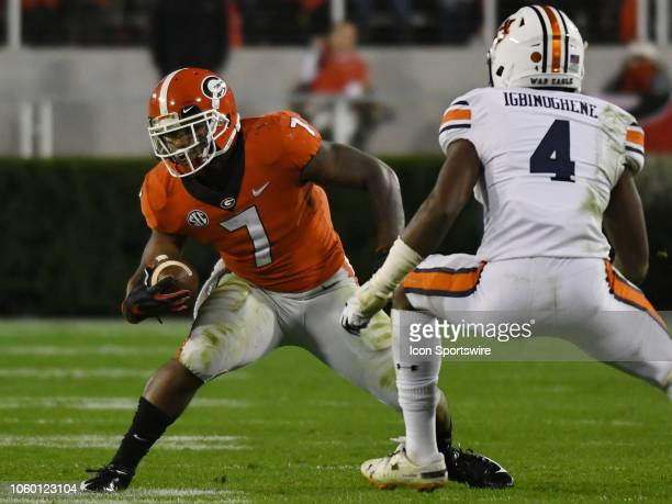 Georgia Bulldogs Running Back D'Andre Smith rushes the ball as Auburn Tigers Defensive Back Noah Igbinoghene sets up to make a play during the game...