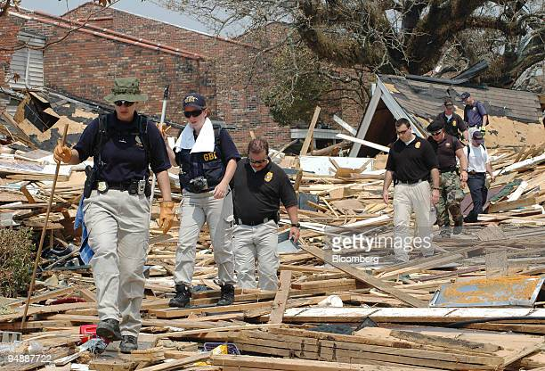 Georgia Bureau of Investigation officers from left Jerri Lynn Coody Kelli Bowles Robert Corn and John Grantham hike through debris with other search...