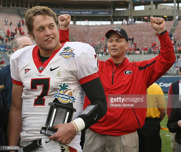 Georgia coach Mark Richt chants 'one more year' in the background as quarterback Matthew Stafford is awarded the MVP trophy following their 2412...