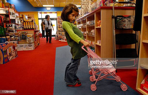 Georgia Cutrona 4 1/2 pauses to examine a shelf of toys at Toys Co while playing with a doublestroller November 26 in Charlotte North Carolina This...