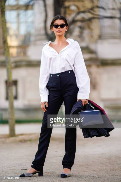 Georgia Fowler wears sunglasses a white shirt balck pants a bag outside Elie Saab during Paris Fashion Week Womenswear Fall/Winter 2018/2019 on March...