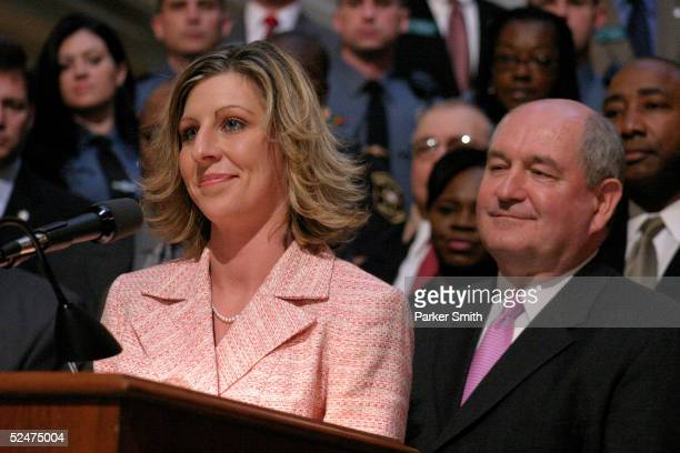 Georgia Governor Sonny Perdue looks on as Ashley Smith speaks during a presentation of a $10000 she recieved as a reward from the State of Georgia...