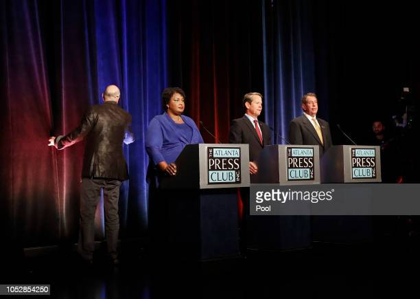 Georgia gubernatorial candidates Democrat Stacey Abrams Republican Brian Kemp and Libertarian Ted Metz wait as stage crew look for the source of a...
