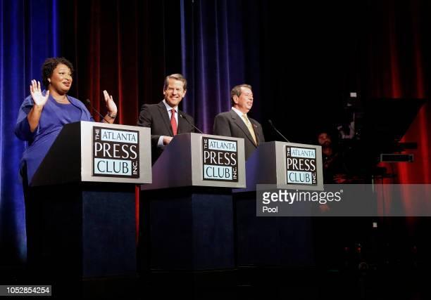 Georgia gubernatorial candidates Democrat Stacey Abrams Republican Brian Kemp and Libertarian Ted Metz react as a fire alarm interrupts their debate...
