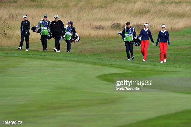 Georgia Hall and Laura Davies of Great Britain walk with Noemi Jimenez and Silvia Banon of Spain on hole one during match 1 of Group A during day one...